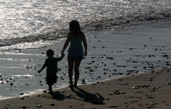 mom and son walking along the seashore
