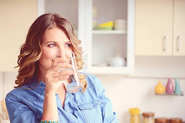 woman-drinking-water-kitchen